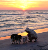 Lisa enjoying a sunset at the beach with her dogs